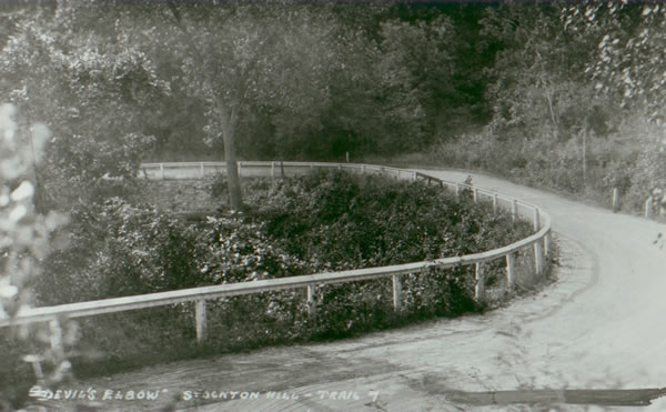 "A postcard showing the ""Devil's Elbow"" as it appeared between 1921 and 1932. Note the wood guard rails, and the stone retaining wall."