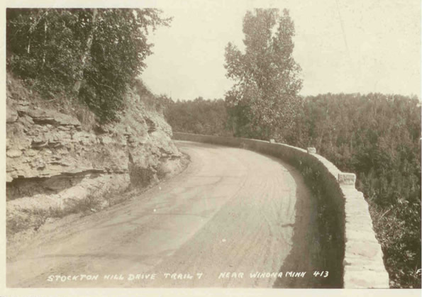 "Looking back to the east on the first curve into the ""Devil's Elbow"". Note the lone tree, which is possibly the same one as seen in the previous photo. You can also see how the road is half concrete and half gravel. Note how the caption says ""Trail 7"", referring to Constitutional Route 7, the original designation for U.S. 14 in Minnesota."