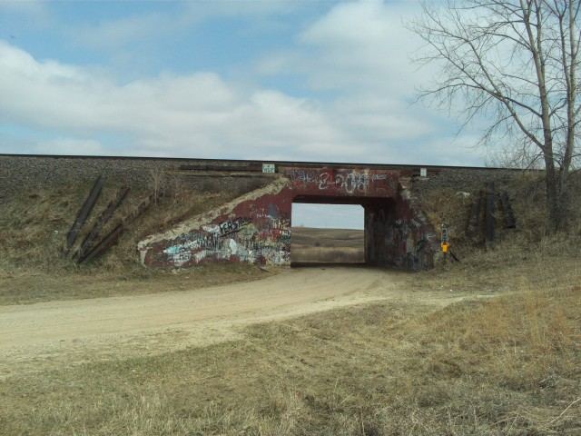 "Another railroad underpass, east of Winnipeg Junction, with ""Territorial Pissings"". The road makes a rather sharp curve as it passes under the tracks."