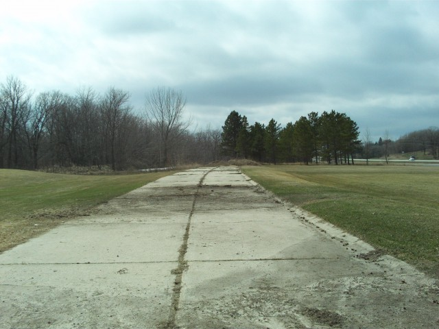 A short section of the old concrete pavement survives just west of Boyer Lake on the south side of the modern highway.